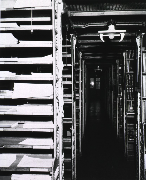 <p>Interior view: Stacks are on each side of a grated floor.  Serials are shelved in the foreground.  In the background are stairs leading up to the next level.  A window is at the end of the walkway.</p>