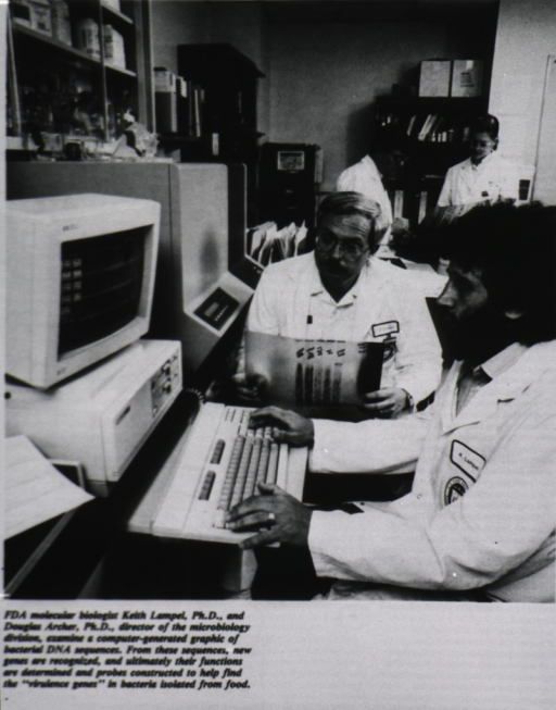 <p>Two men sit at a computer console in a laboratory.</p>
