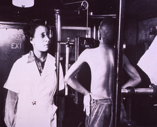 <p>View from behind of a boy receiving a chest x-ray; a technician stands to the left.</p>
