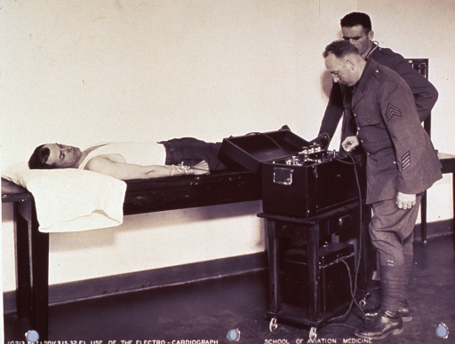 <p>A man is lying on a special table and is hooked up to the electrocardiograph machine.  Two other men are standing next to the machine, one of whom is touching a switch on the machine.  The other man has a stethoscope around his neck.  All three men are looking at the machine.  The two men standing next to the machine are in full uniform.</p>