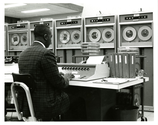 <p>John Smith types in computer commands to be performed and processed by magnetic tape in the OCCS computer room.</p>