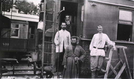 <p>Four men stand outside of the dining car.</p>