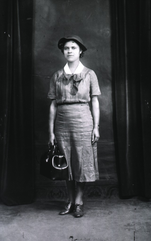 <p>Ethel May Jones, an African American public health nurse, is dressed in her uniform and carrying her bag, in her role as asst. midwife - teacher, State Board of Health.</p>