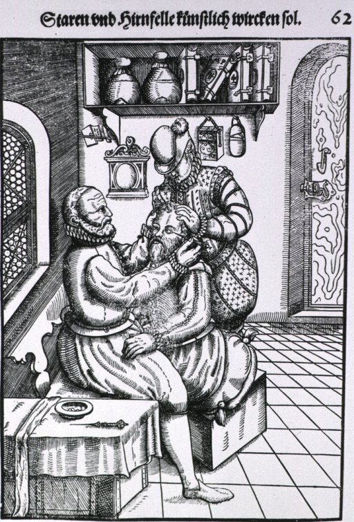<p>Interior of a physicians' office: a patient, sitting on a cushion on a box, is having a cataract removed from his left eye; the surgeon sits before him and an assistant stands behind the patient immobilizing his head. Books and glassware are on a shelf.</p>