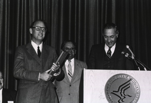 <p>Richard Schweiker, secretary of the Dept. of Health and Human Services (DHHS), is standing in front of microphones at a podium with the DHHS logo.  Donald S. Fredrickson is holding the DHHS Distinquished Service Award.</p>