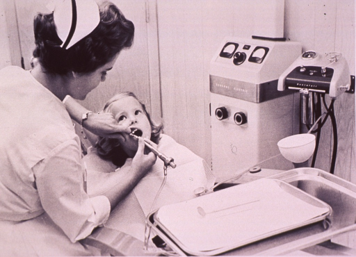 <p>A dental assistant is cleaning a little girl's teeth.</p>