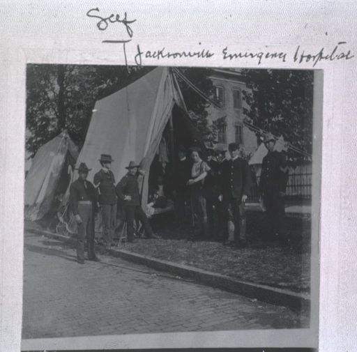 <p>Exterior view showing group of officers and enlisted men standing around a tent at the Jacksonville Emergency Hospital.</p>