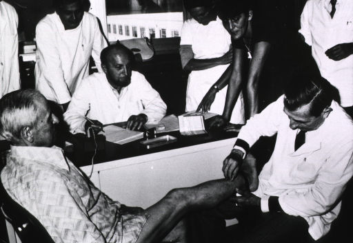 <p>Interior view: a man is inserting needles into the leg of an old man; several people are observing the procedure.</p>