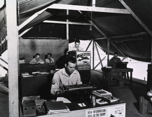 <p>Servicemen and a woman sit at desks in an open-air tent and work at typewriters.</p>