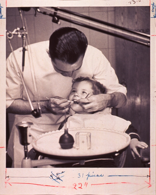 <p>A dentist is examining the teeth of a child sitting in the dental chair.</p>
