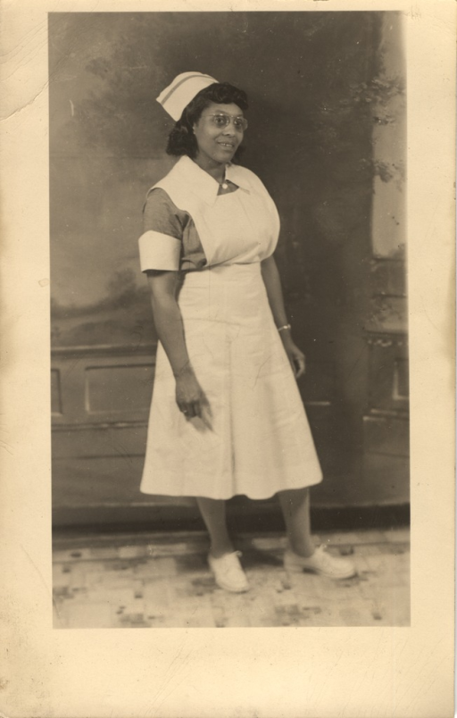 <p>Postcard featuring a black and white photograph of an African American nurse. She is wearing glasses.</p>