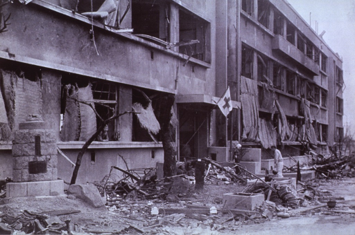 <p>Exterior view of the Fukuromachi School (700 meters).  This building, not far from the center of the explosion, was one of the few left standing in the area.  It was put to immediate use as an aid station.  Note mats used for shelter.</p>