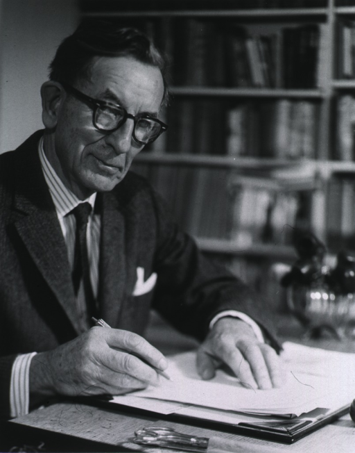 <p>Half-length, seated at desk, full face, wearing glasses, holding pen in right hand.</p>