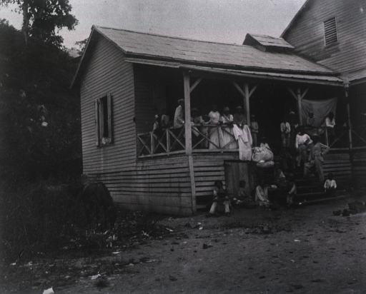 <p>View of men, women, and children on the front porch and stair area of a house in Firmeza.</p>