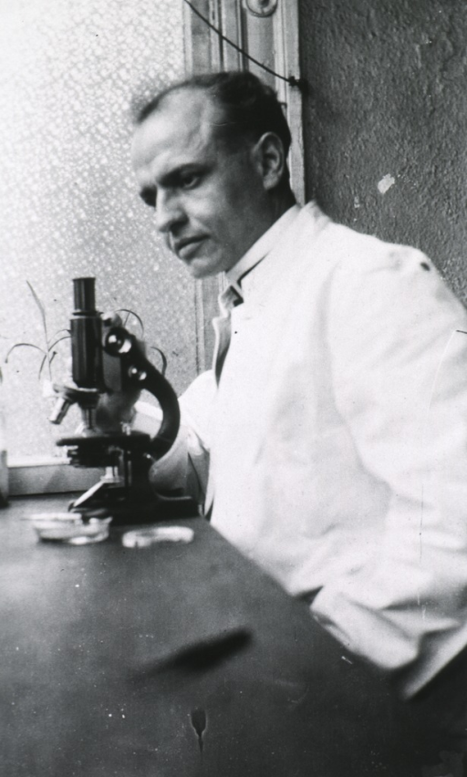 <p>Half length; head to left; white coat; before microscope in laboratory.</p>