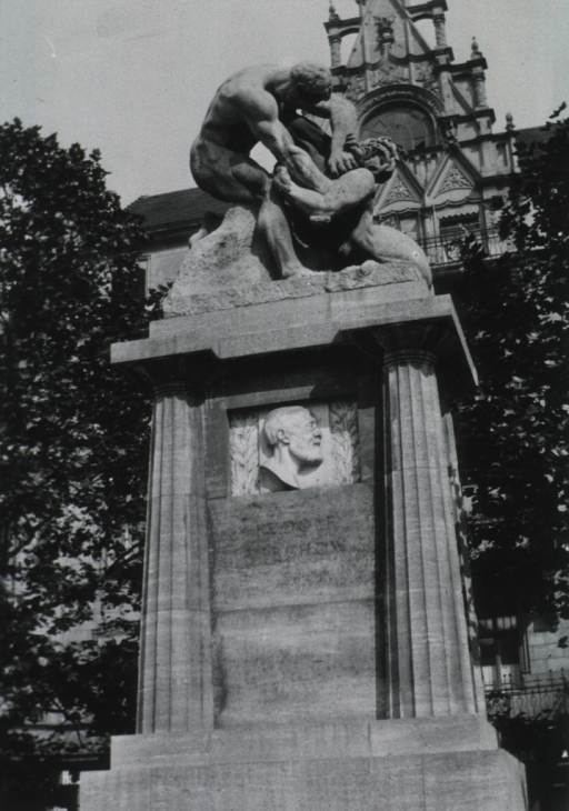 <p>Monument in front of cathedral; has relief of Virchow's head, in middle of monument; Doric columns supporting man wrestling with lions.</p>