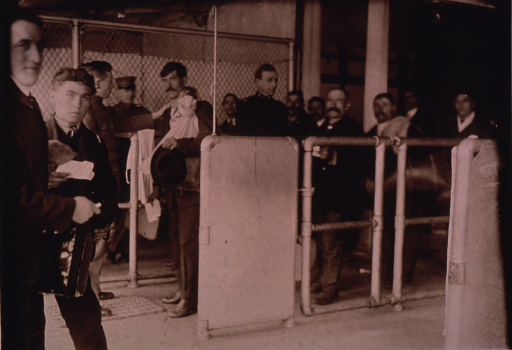 <p>Interior view: Dr. White and others at gate examining immigrants entering this country at the U.S. Quarantine Station at Ellis Island(?).</p>