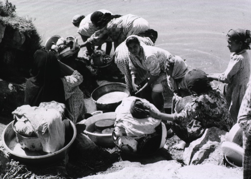 <p>A group of women are washing pots, pans, and clothing in canal water.</p>
