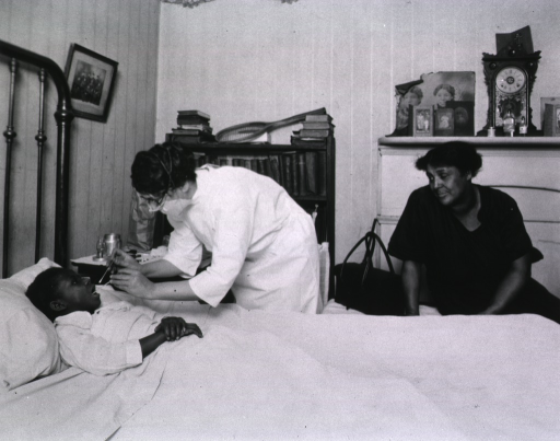<p>Bedside scene, showing a nurse examining the throat of a child.  The mother observes from the foot of the bed.</p>