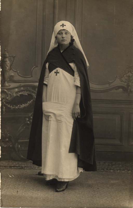 <p>Postcard featuring a black and white photograph of a full length portrait of a French nurse wearing a long white dress, a head scarf with a Red Cross symbol on it, and a dark-colored cape.</p>