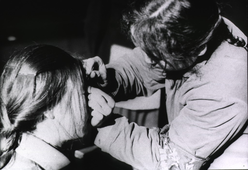 <p>A young woman is inserting a needle above the nose of another young woman.</p>