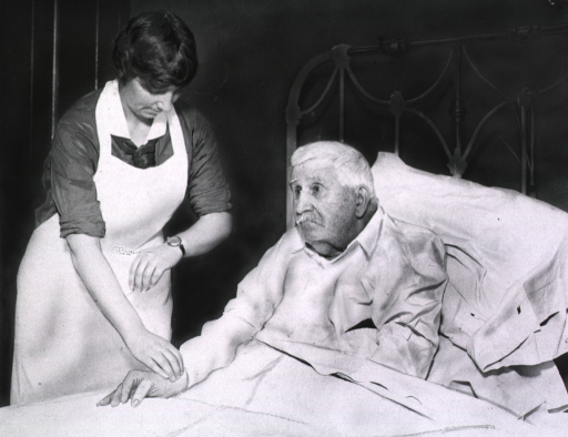 <p>Bedside scene, showing nurse taking the pulse of an old man.</p>
