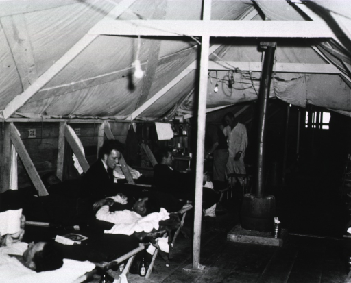<p>Two connecting ward tents are shown.  Wounded servicemen lie on cots.</p>