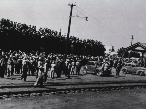 <p>Close-up of crowds at a processing center in Chihuahua, Mexico. Many people are standing along the railroad tracks outside a train station, some are sitting on top of boxcars.</p>