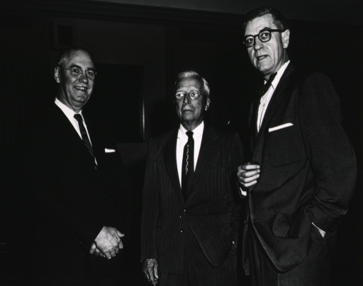 <p>Rolla E. Dyer, director of the National Institutes of Health from 1942-1950, Vannevar Bush, supervisor of the Manhattan Project, and James A. Shannon, director of the National Institutes of Health from 1955-1968, are standing together.  The room is poorly lighted.  There is a picture on the wall between two windows.</p>