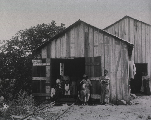 <p>Women and children gather in the entrance of a storage facility.  Railroad tracks lead into the building.</p>