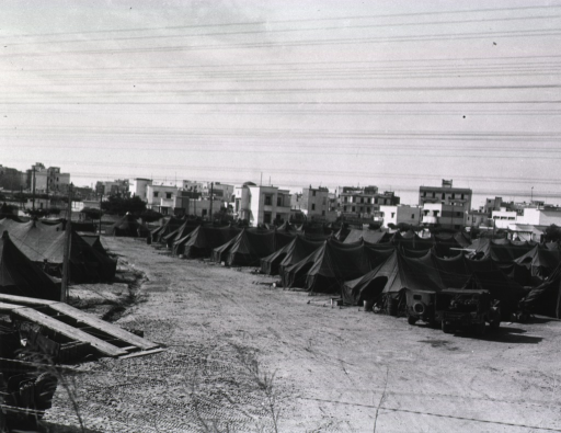 <p>Several pitched tents are shown in the foreground. Several army jeeps are parked near the tents. In the background low buildings are visible.</p>