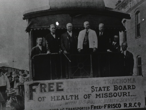 <p>Several men are standing on the back of a railroad car on which is a large sign announcing a free trachoma clinic.</p>