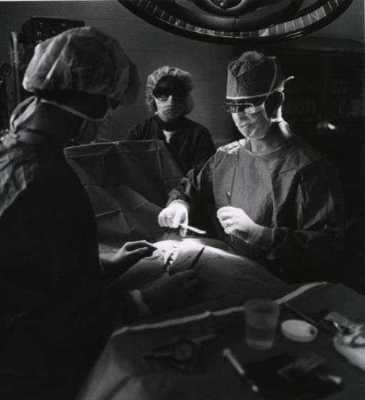 <p>Surgeon and two assistants in an operating room; all are gowned, capped, and masked.</p>
