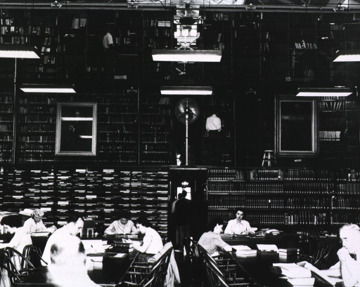 <p>Interior view of three tiers of stacks from the main floor looking toward the ceiling: on the ground floor are patrons sitting at tables, shelving with journals on one side of a doorway and books on the other side, and a woman is sitting at Robert B. Austin's desk.  On the second tier are book stacks, a floor fan, and large portraits hanging from the railing.  On the third tier there are book stacks and a table fan.  A pole with four light bulbs and reflectors run parallel to the top of the stacks.</p>