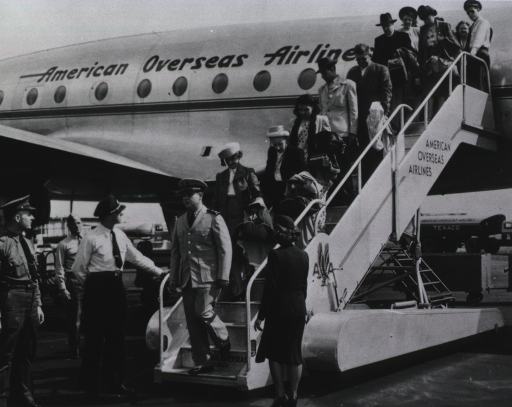 <p>PHS officer and overseas passengers on stairway at the side of the airplane.</p>