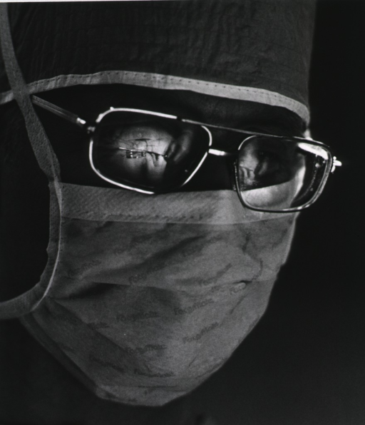 <p>Close-up of the surgeon's face where the reflection of the operative field can be seen in his eyeglasses.</p>