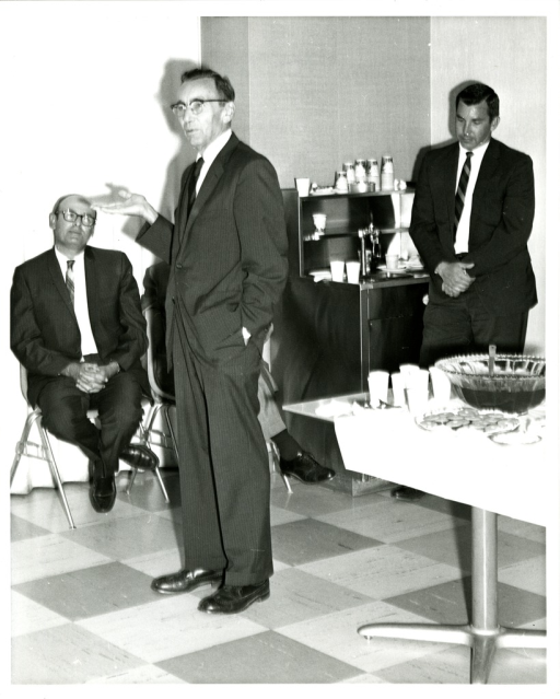 <p>National Library of Medicine Director Dr. Martin Cummings, MD, (rear left) attends a party honoring his colleague Mr. Scott Adams (front center).</p>
