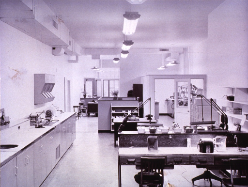 <p>Interior view:  A partitioned room with equipment is to the side of a large open room with laboratory tables which opens to a reception area in the background.  The room is lighted by fluorescent bulbs.</p>