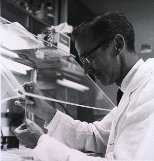 <p>Half length, left profile, in lab coat using a pipette under a hood, wearing glasses.</p>