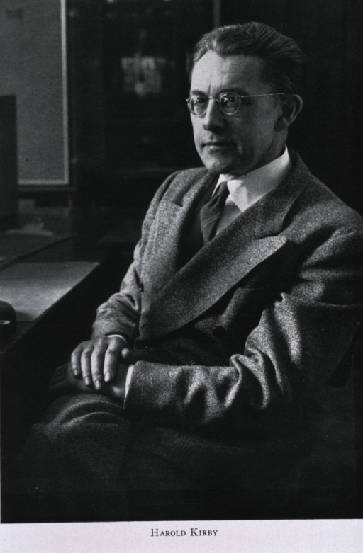 <p>Three-quarter length, seated, left pose; wearing glasses; hands together in front.</p>