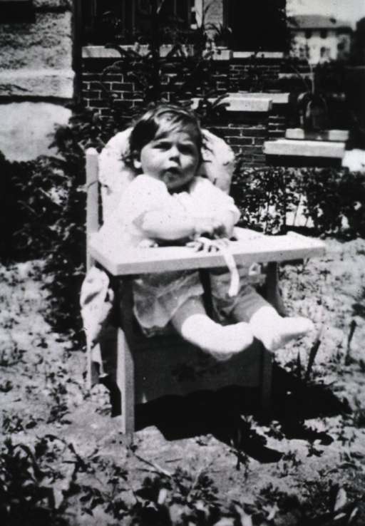<p>Exterior view showing the baby, Eileen, seated in a chair.</p>