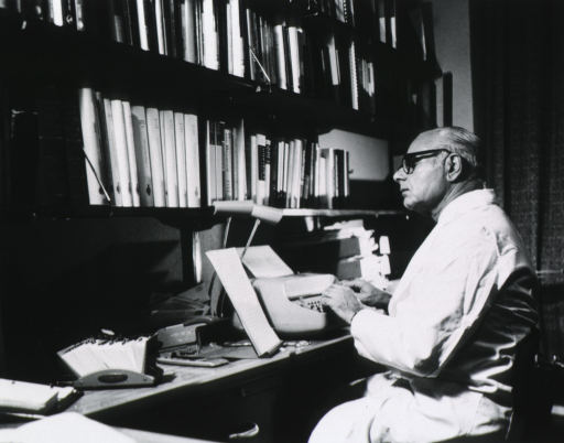 <p>Half length, left profile; wearing glasses and lab coat; seated at desk, typing.</p>