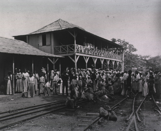 <p>Many refugees, mostly women and childre, gather on the railroad tracks next to a building.  Two soldiers are in the crowd.</p>