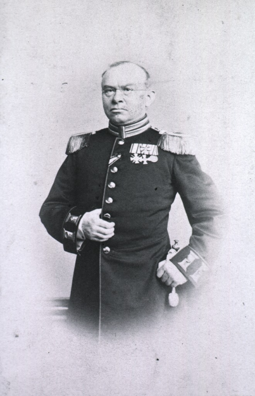 <p>Standing, three quarter length, full face in uniform, one hand on hilt of sword.</p>