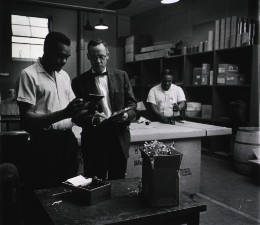 <p>Interior of Building 13.  Showing Jacob Kirkland, V.A. White, packers, and David S. Smith, Head of Shipping and Receiving.</p>