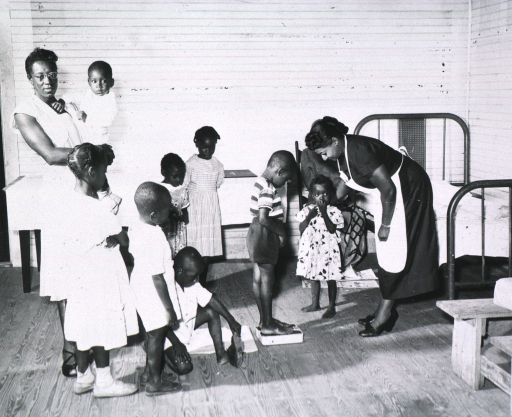 <p>African American children are waiting their turn to be weighed by Eugenia Broughton at the school clinic in Cainhoy, S.C., 1949.</p>