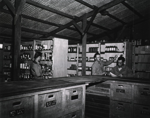 <p>Three servicemen are shown at work among the stocked shelves of a supply office.</p>
