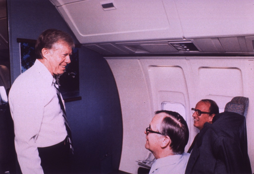 <p>President Jimmy Carter is standing speaking with Robert Berglund, secretary of agriculture, and Dr. Donald S. Fredrickson, director of the National Institutes of Health (NIH).  Secretary Berglund's coat is over the back of his seat.  They are in Air Force One.</p>