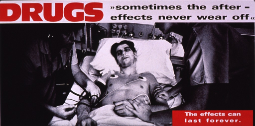 <p>Predominantly b&amp;w poster with multicolor lettering and red highlights.  Title at top of poster.  Visual image is a b&amp;w photo reproduction showing a man lying in a hospital bed.  He is tended by two healthcare workers.  He has a tube in his nose and several electrodes attached to his torso.  Caption in lower right corner; publisher information in lower left corner.</p>