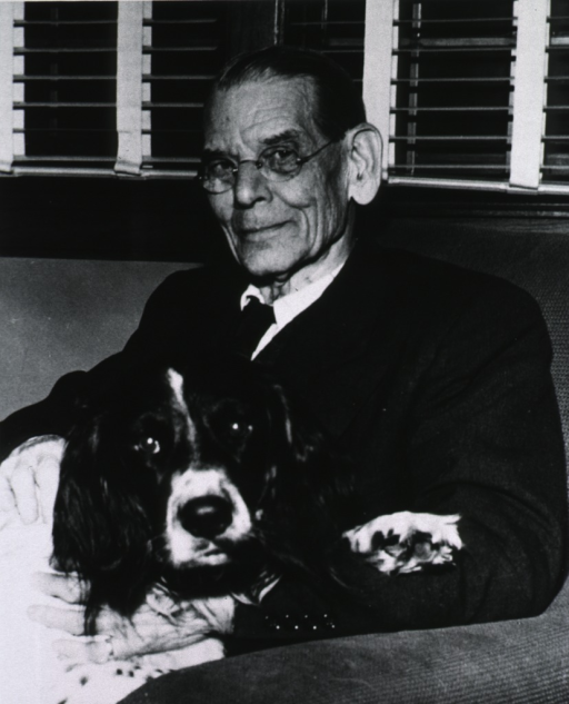 <p>Half-length, seated with dog on lap, left pose, full face; wearing glasses.</p>